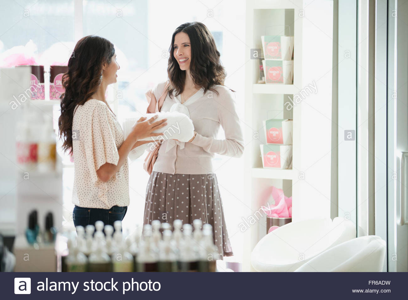 women discussing beauty products at spa - Stock Image