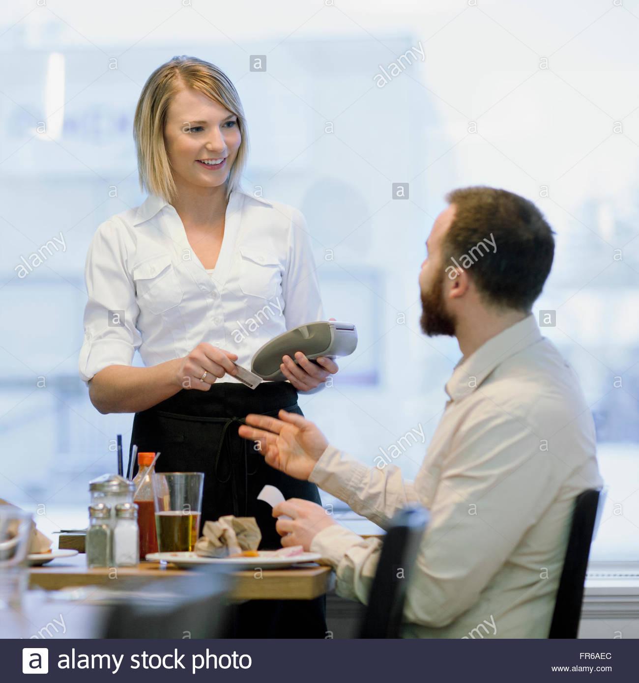 waitress completing debit transaction - Stock Image