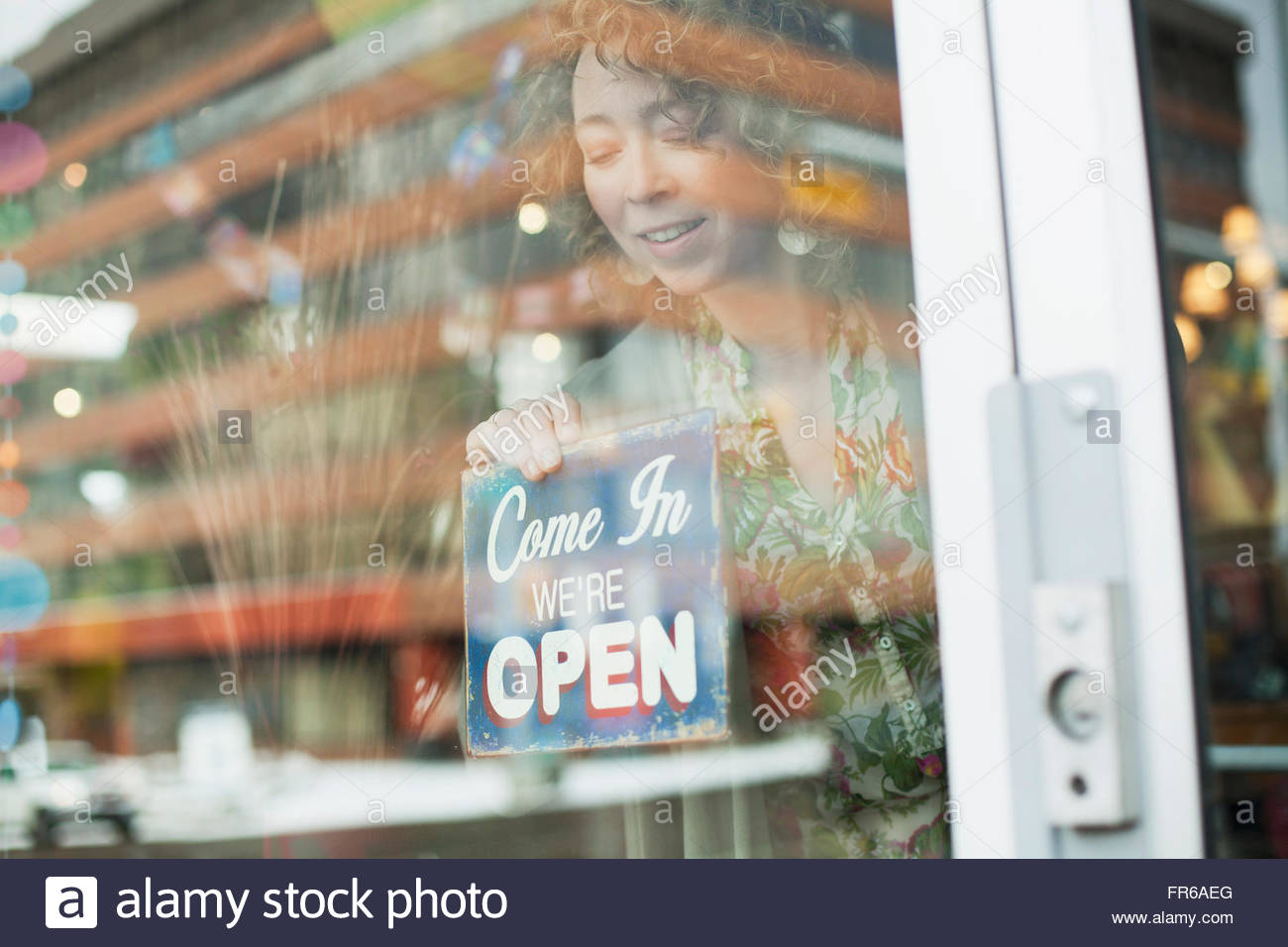 small business owner prepping to open - Stock Image