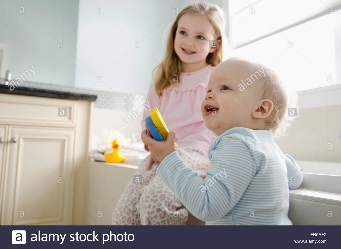 young girl with younger brother in bathroom Stock Photo