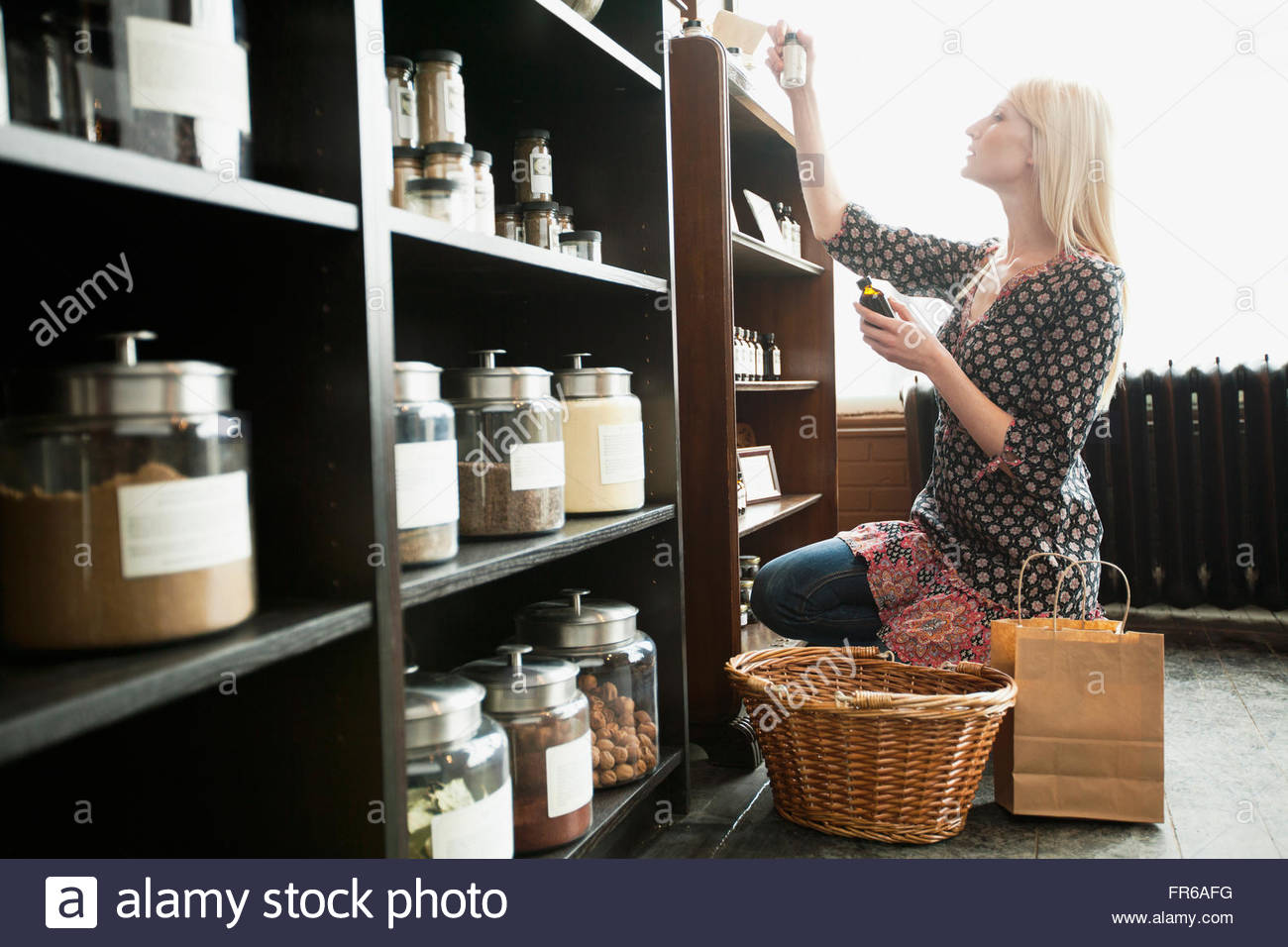 customer choosing spices in retail spice store - Stock Image