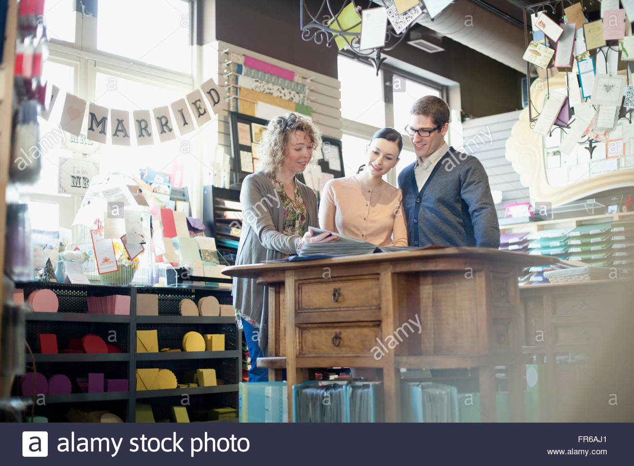 customers in discussion with store merchant - Stock Image