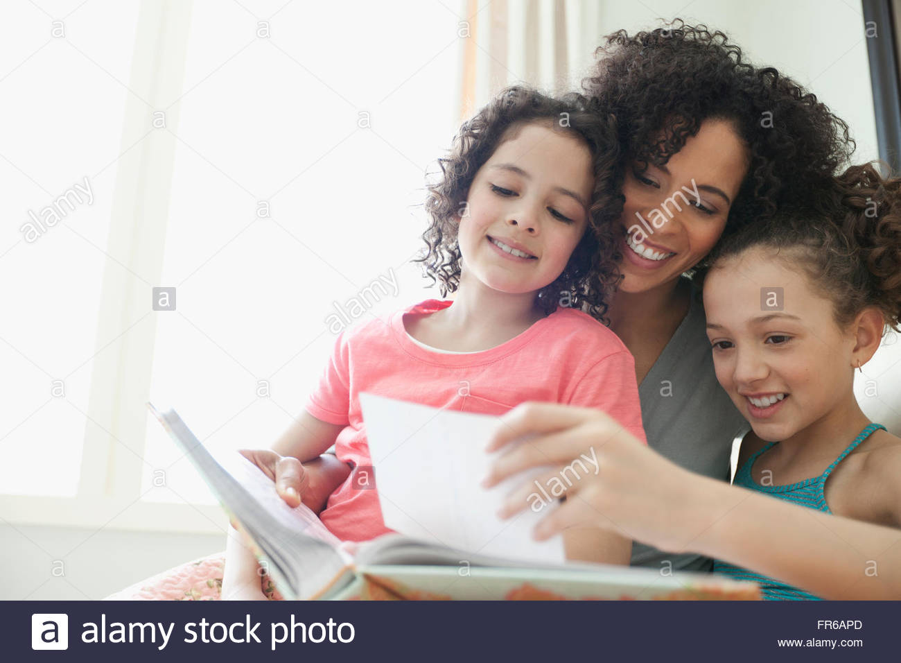 mom and daughters looking at photos - Stock Image