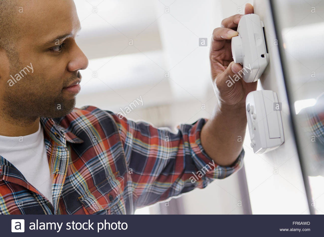 homeowner adjusting new thermostat - Stock Image