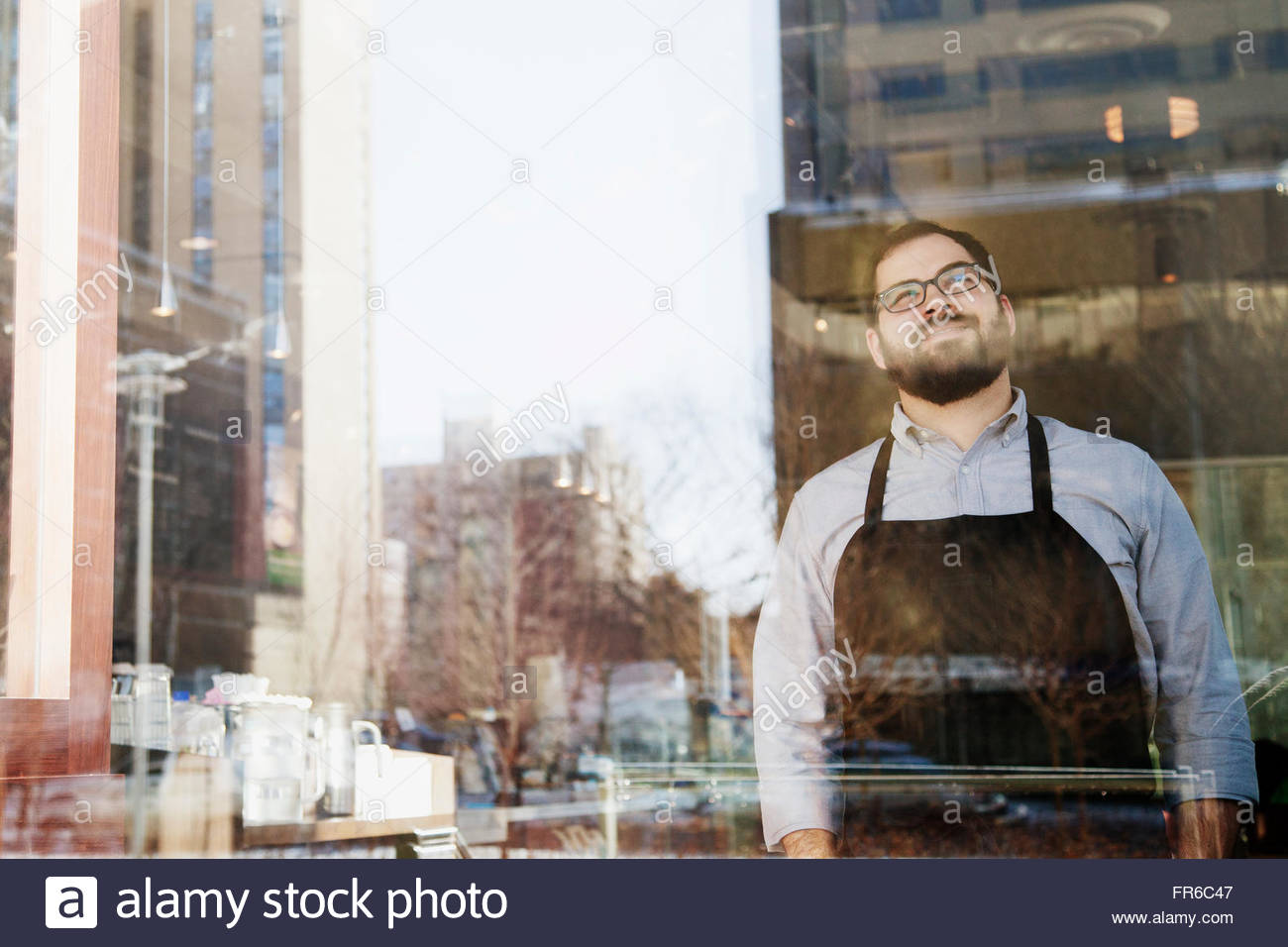 coffee shop owner looking out window - Stock Image