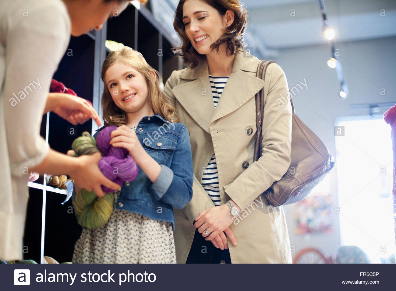 shop owner advising on yarn choice - Stock Image