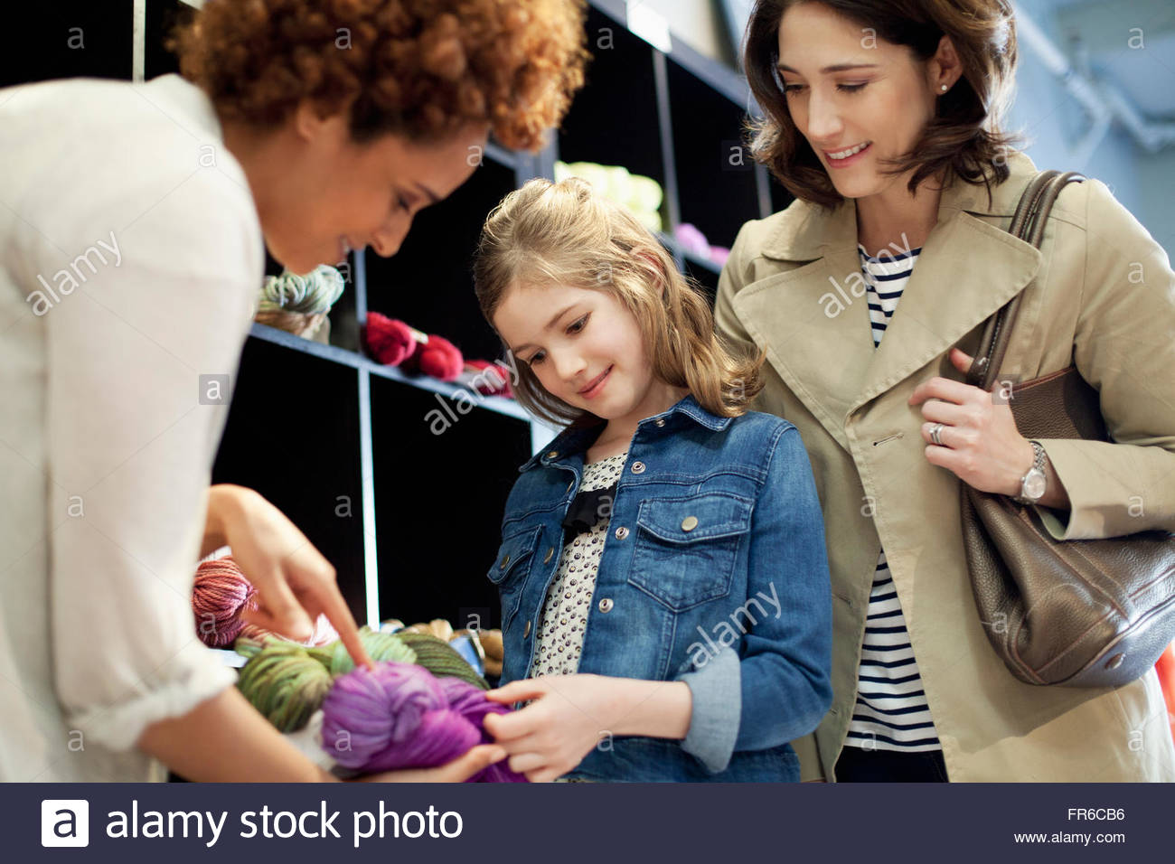 business owner advising on yarn - Stock Image