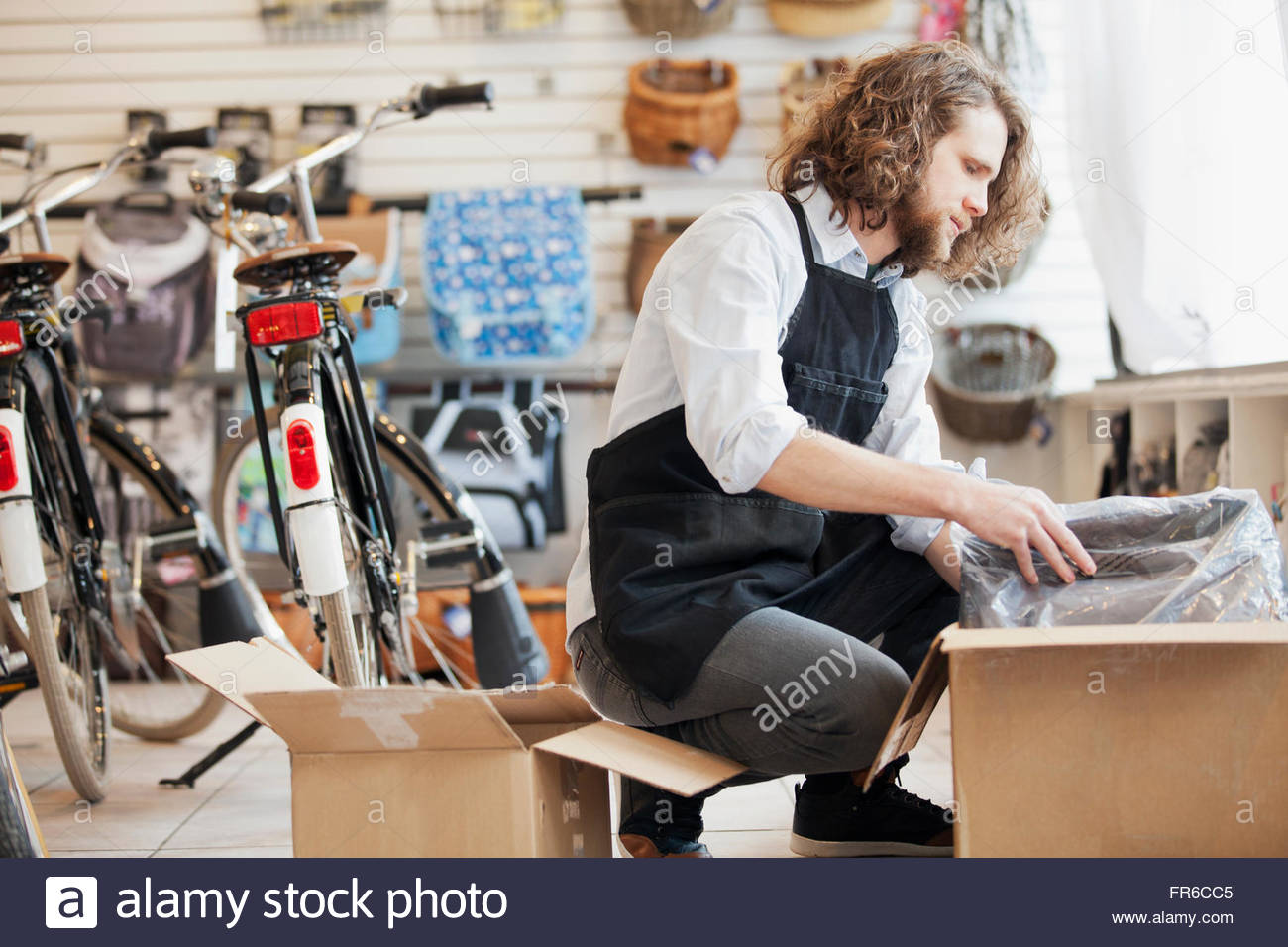 bike shop owner unpacking boxes - Stock Image