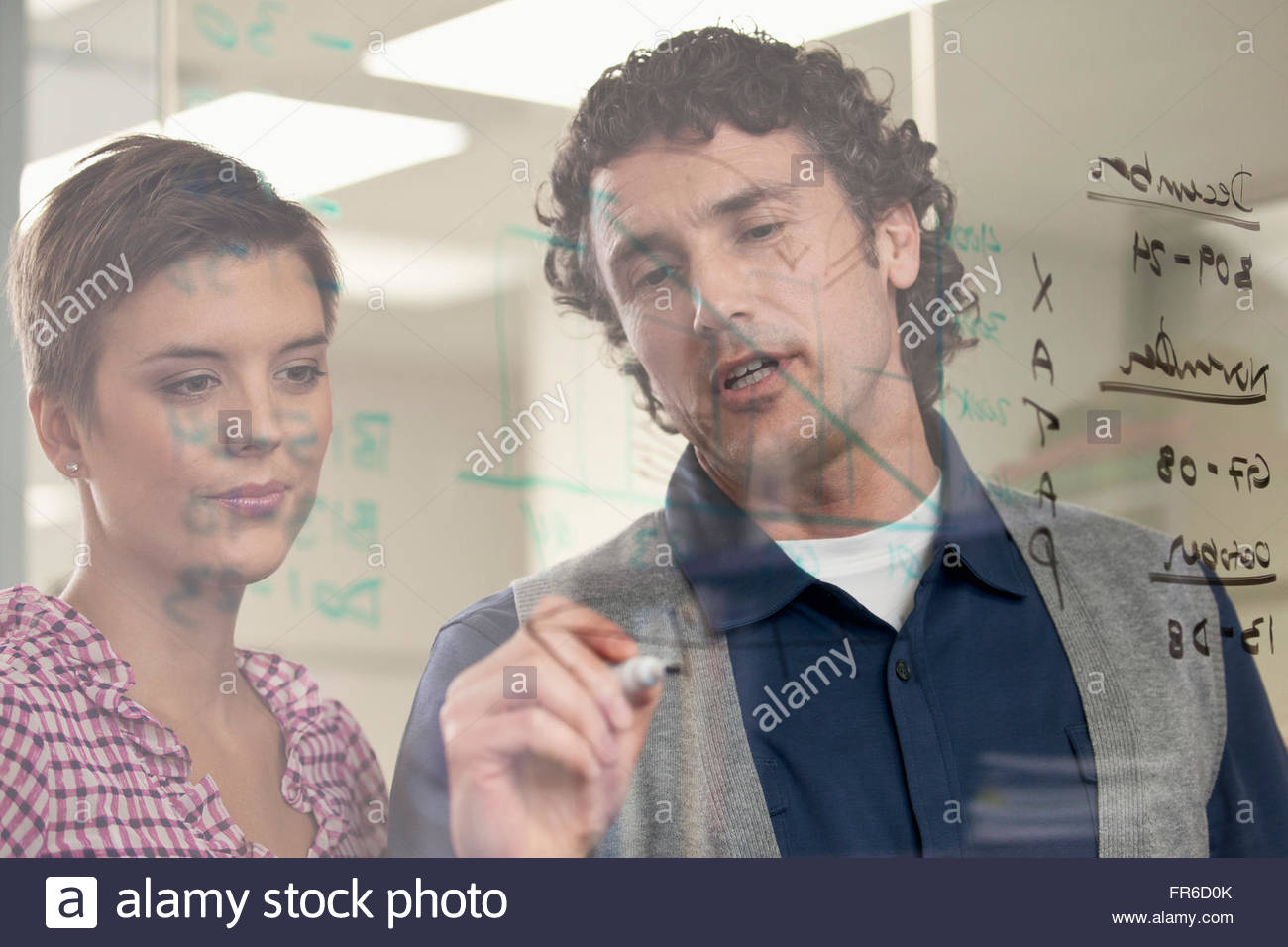reviewing data on glass wall - Stock Image