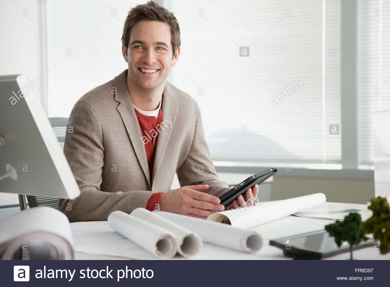 young male architect with blueprints - Stock Image