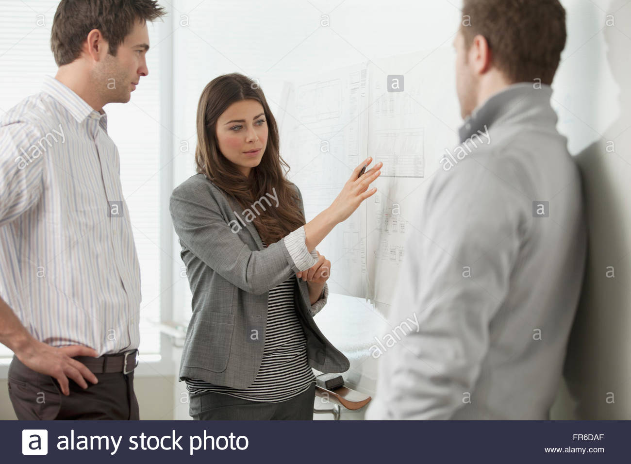 coworkers discussing at whiteboard - Stock Image