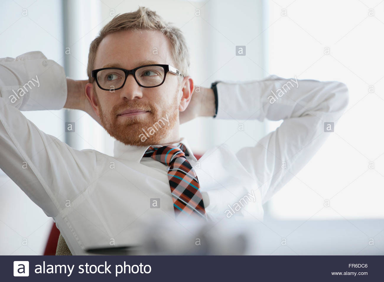 businessman with hands behind head - Stock Image