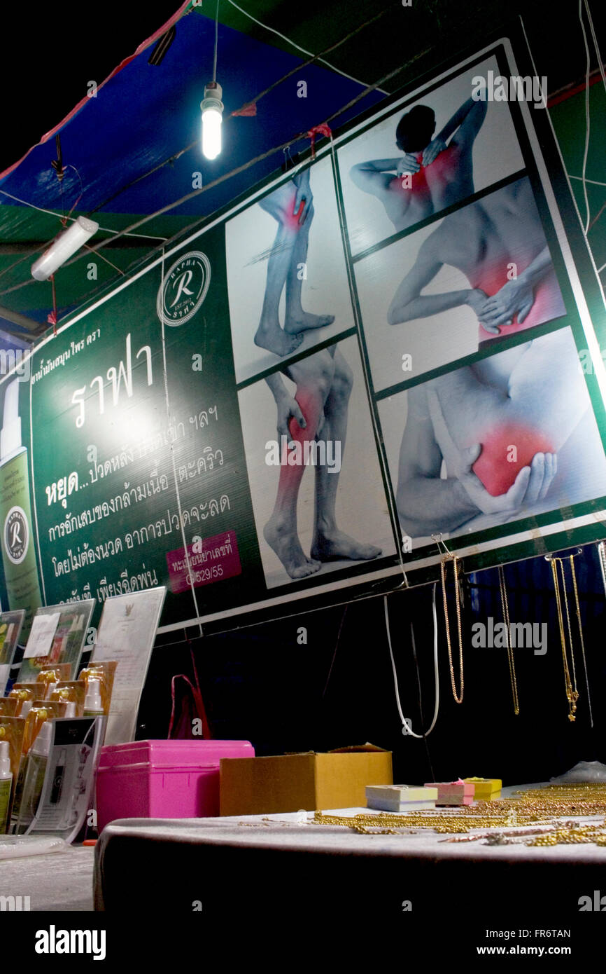 A sign is advertising a spray on product to relieve aches and pains at a street fair in Kampong Cham, Cambodia. - Stock Image