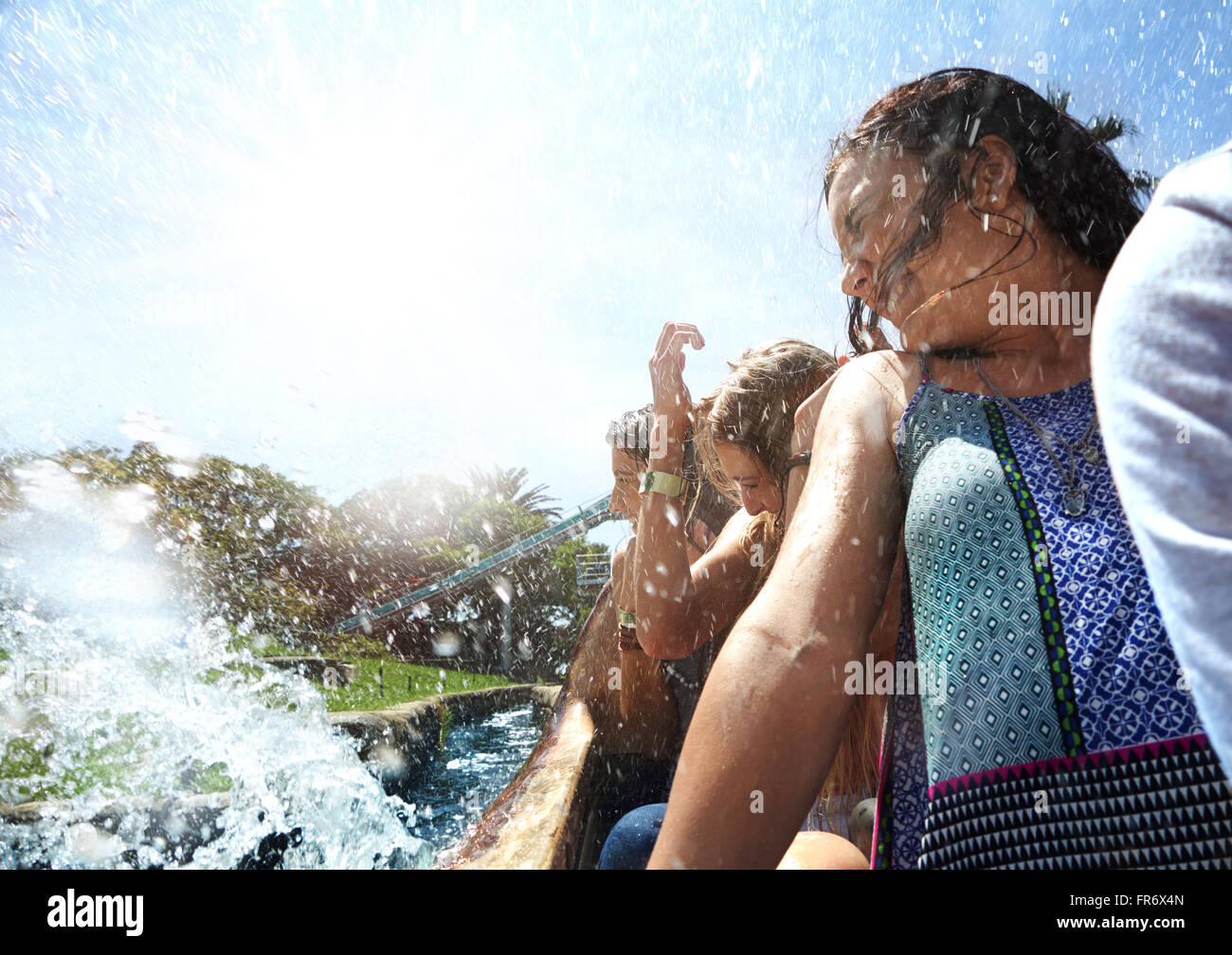Young women getting splashed on water park ride Stock Photo