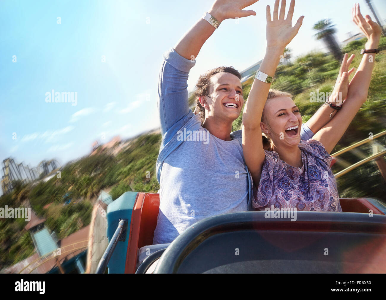 Exhilarated young couple riding amusement park ride - Stock Image