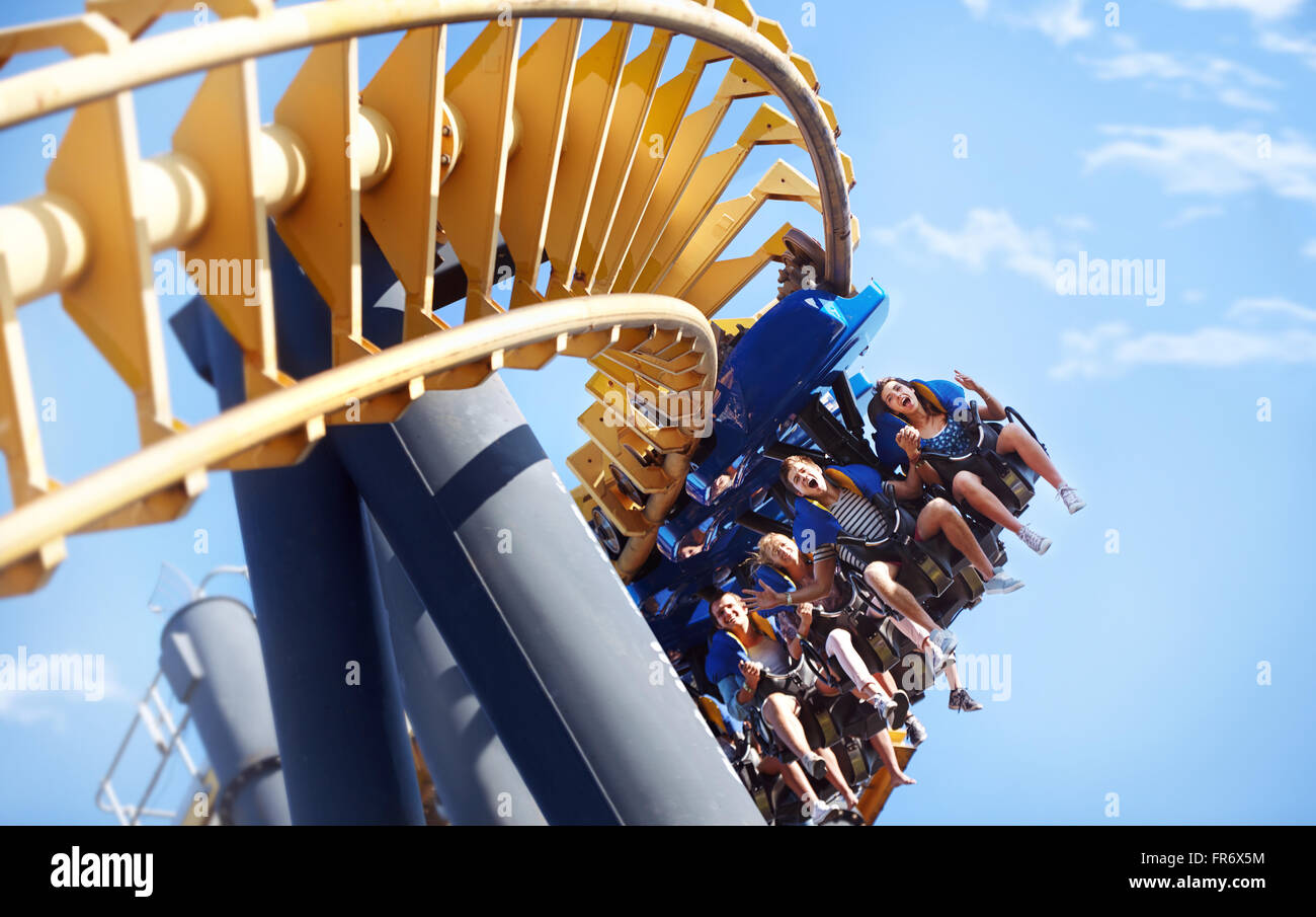 People riding amusement park ride - Stock Image