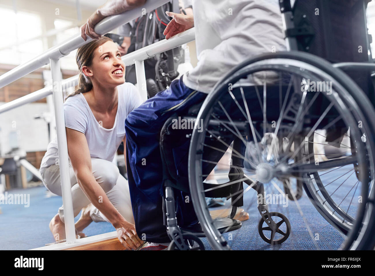 Physical therapist preparing man in wheelchair Stock Photo