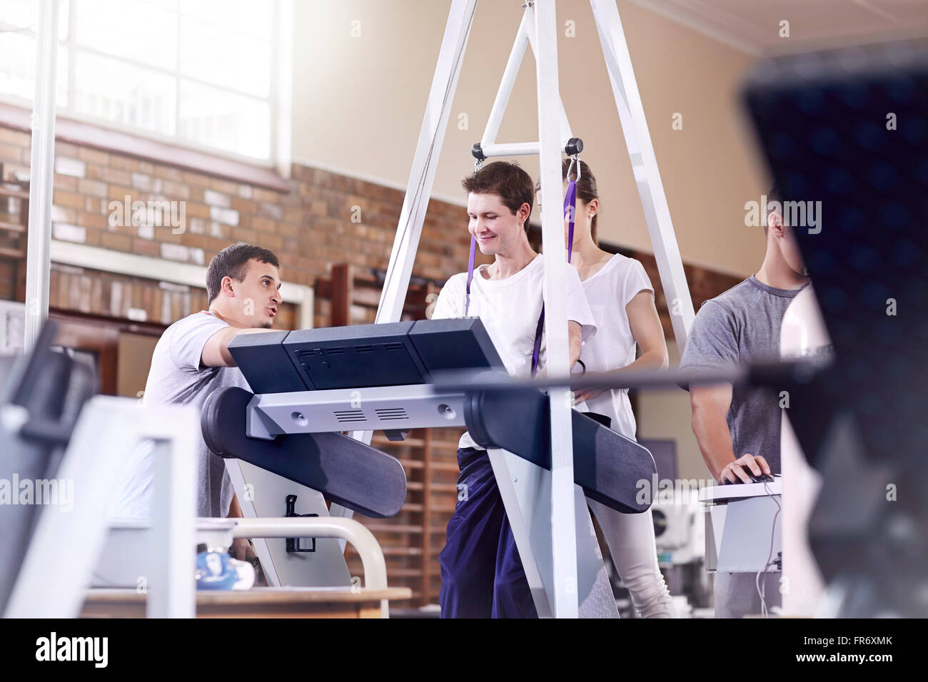 Physical therapists guiding man on treadmill - Stock Image