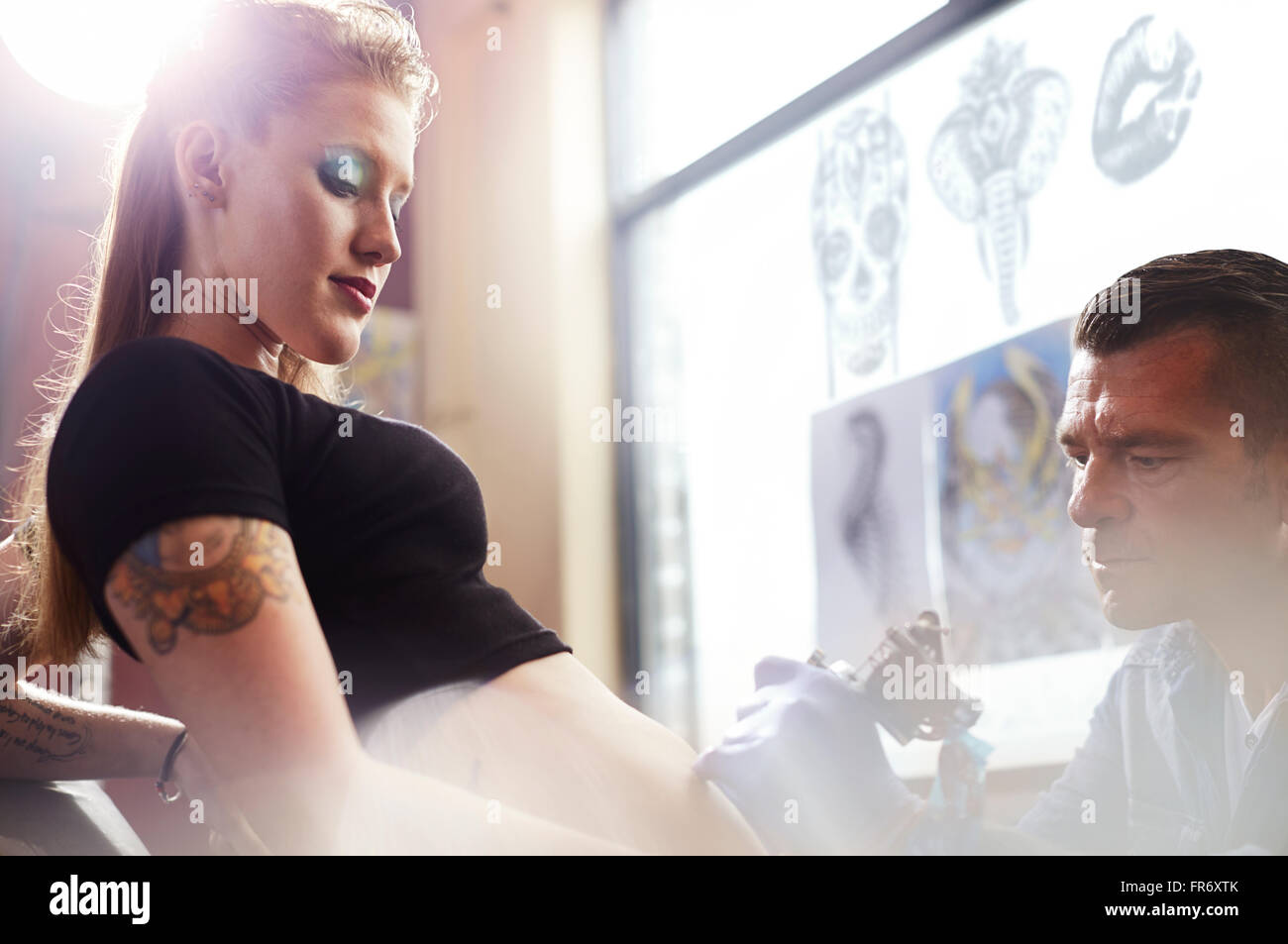 Tattoo artist tattooing woman's stomach - Stock Image