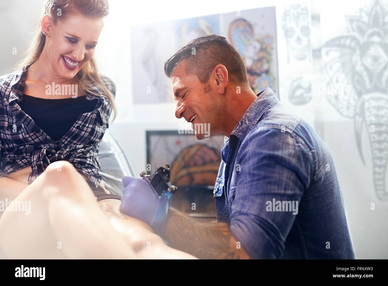 Tattoo artist tattooing woman's thigh - Stock Image