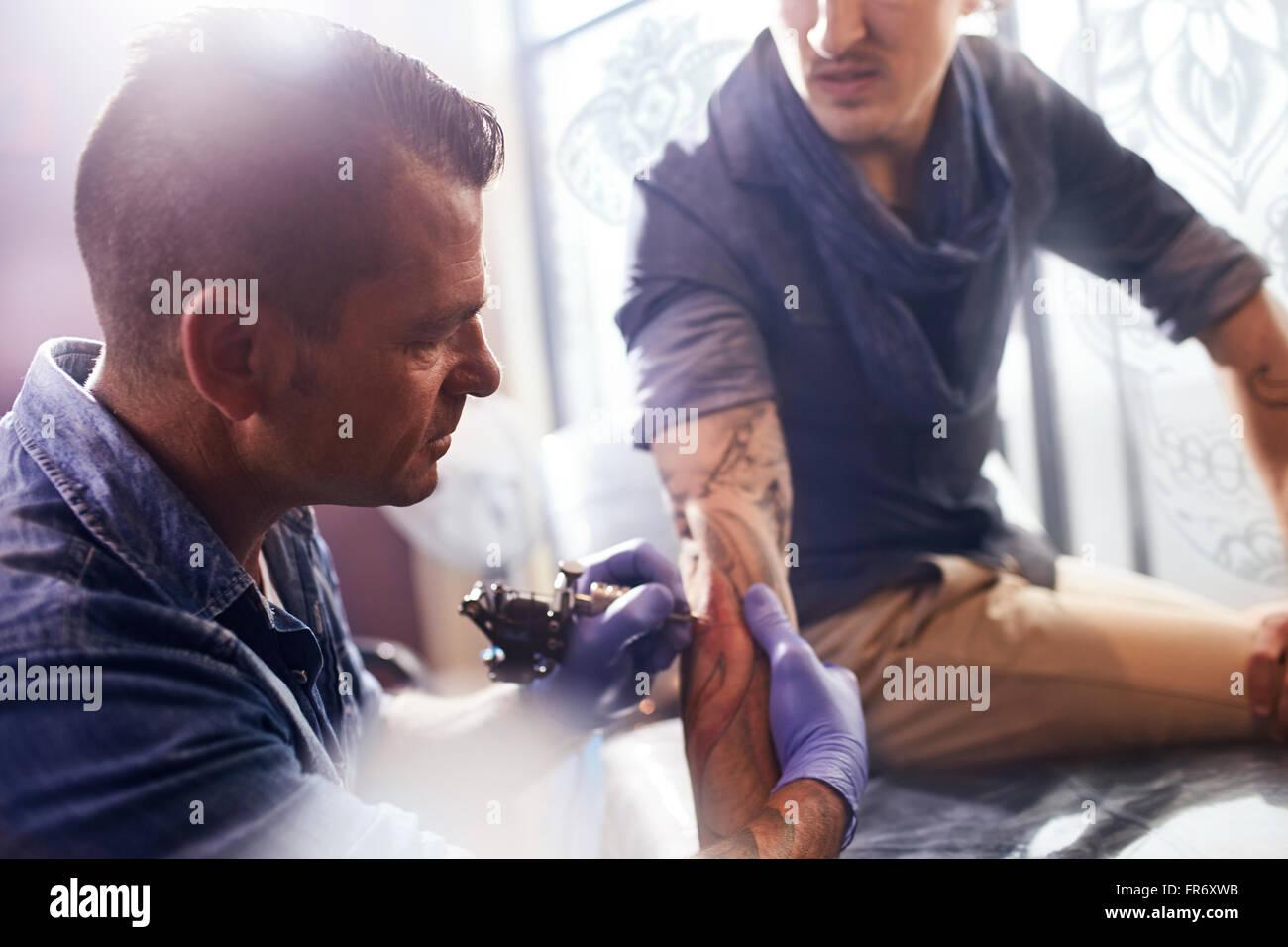 Tattoo artist tattooing man's forearm - Stock Image