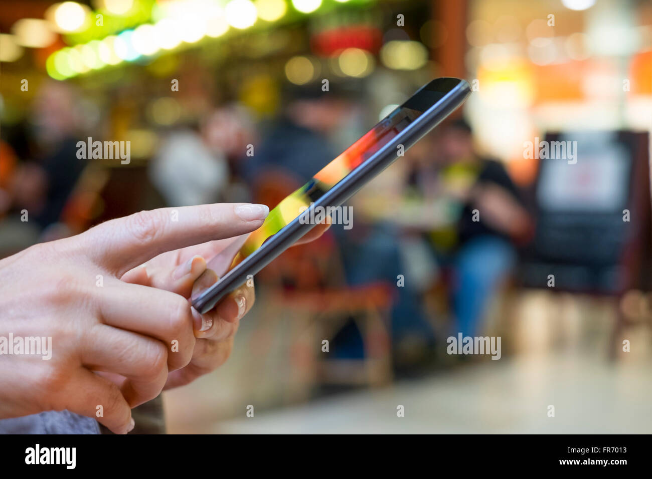 Woman using cell phone in mall. App, texting, sms, message, mail - Stock Image