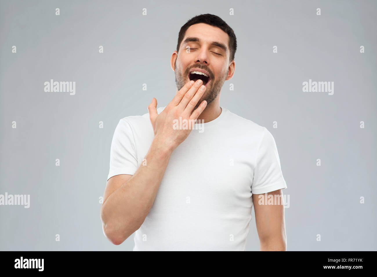 yawning man over gray background - Stock Image