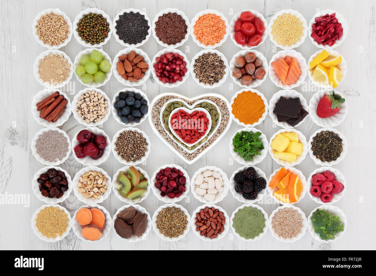 Large superfood selection in porcelain crinkle bowls and heart shaped dishes over distressed wooden background. - Stock Image