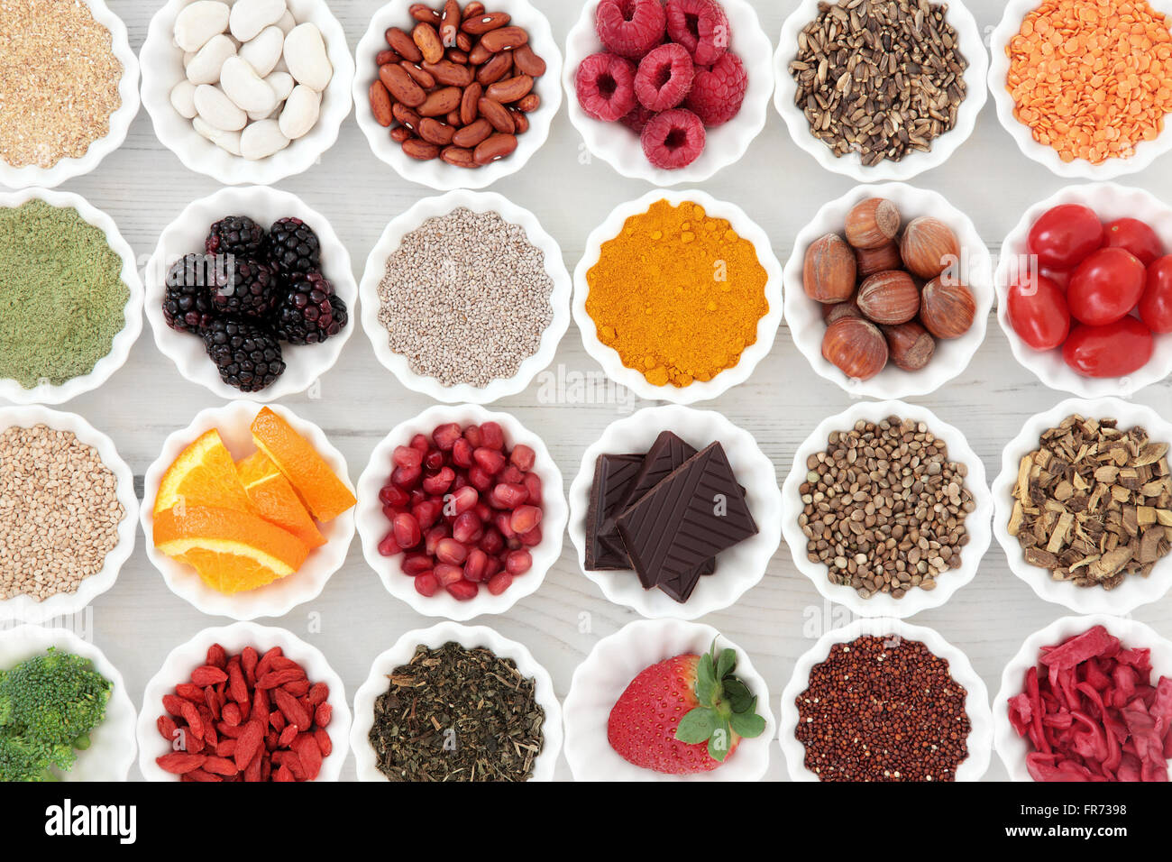 Super health food selection in porcelain crinkle bowls over distressed wooden background. High in vitamins and antioxidants. - Stock Image