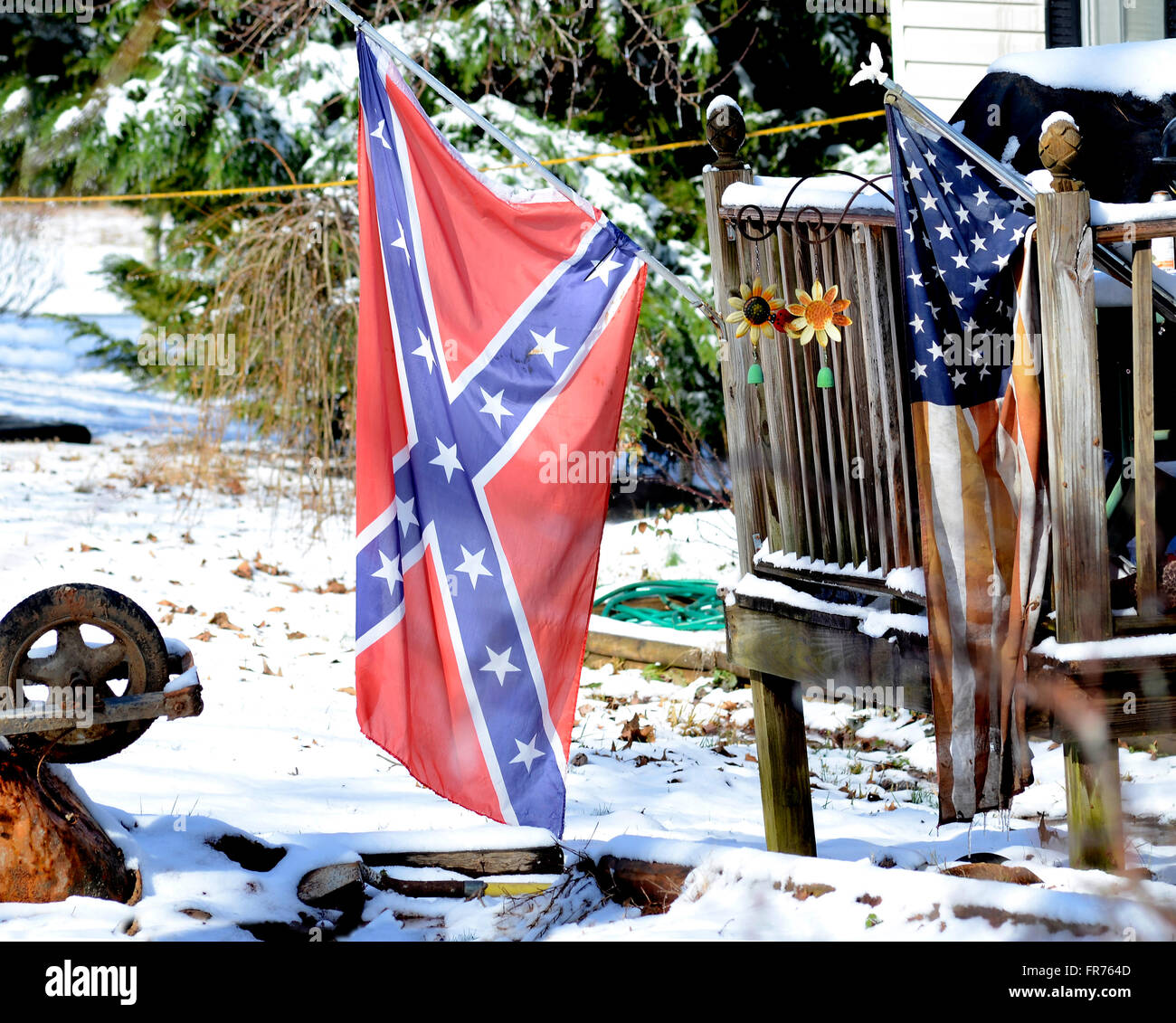 Flags on display in the yard of a messy house on a winter day. - Stock Image