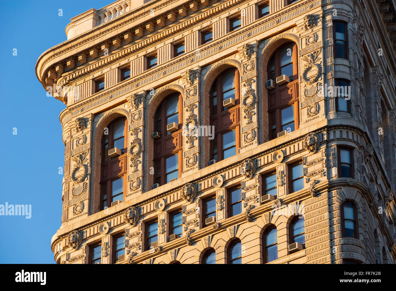 Flatiron Building (Beaux-Arts style) south facade at sunset showcasing intricate terracotta ornaments. Midtown, - Stock Image