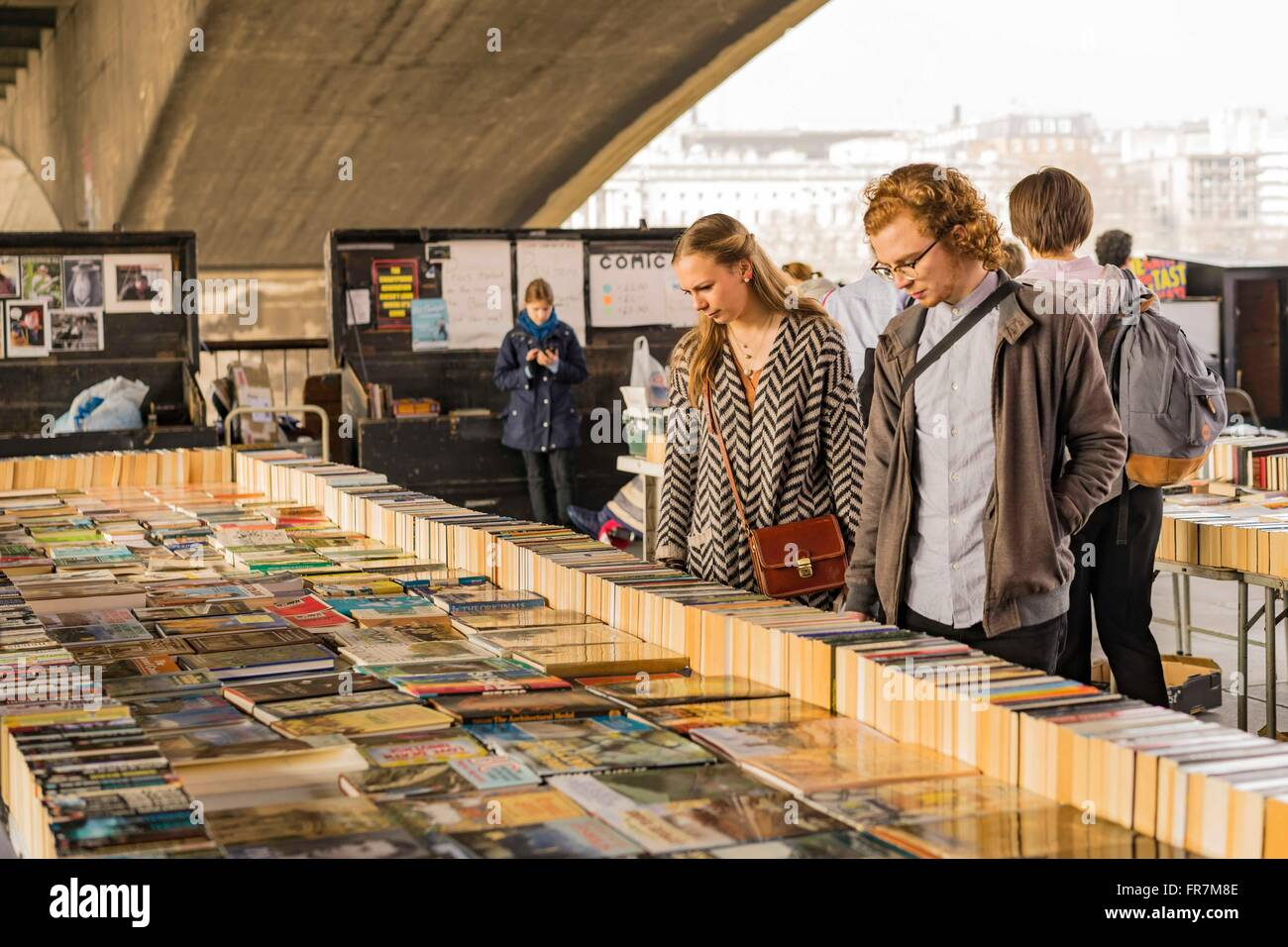 People browse a secondhand book stall under Waterloo Bridge on the South Bank, London - Stock Image