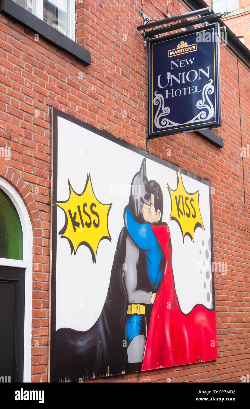 Mural of Batman and Robin kissing on wall of New Union Hotel on Canal Street in Manchester`s Gay village. Manchester. - Stock Image
