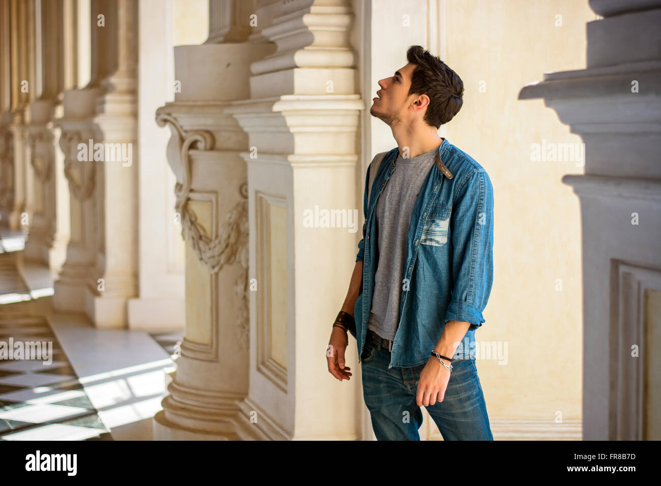 Half Body Shot of a Thoughtful Handsome Young Man, Looking Away Inside a Museum - Stock Image