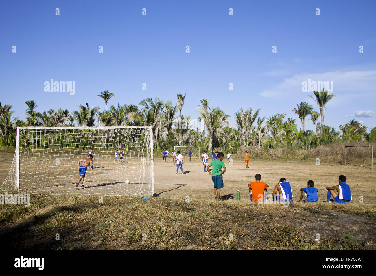 Goalkeeper preparing to kick the ball during a football game in the countryside - Stock Image