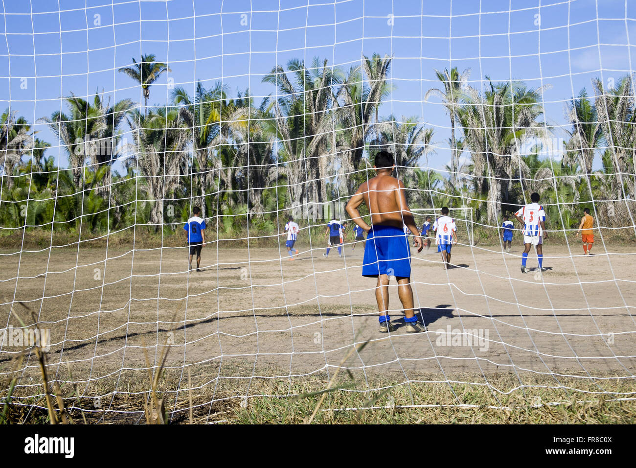 Goalkeeper watching the football match in the countryside with babassu palm trees in the background - Stock Image