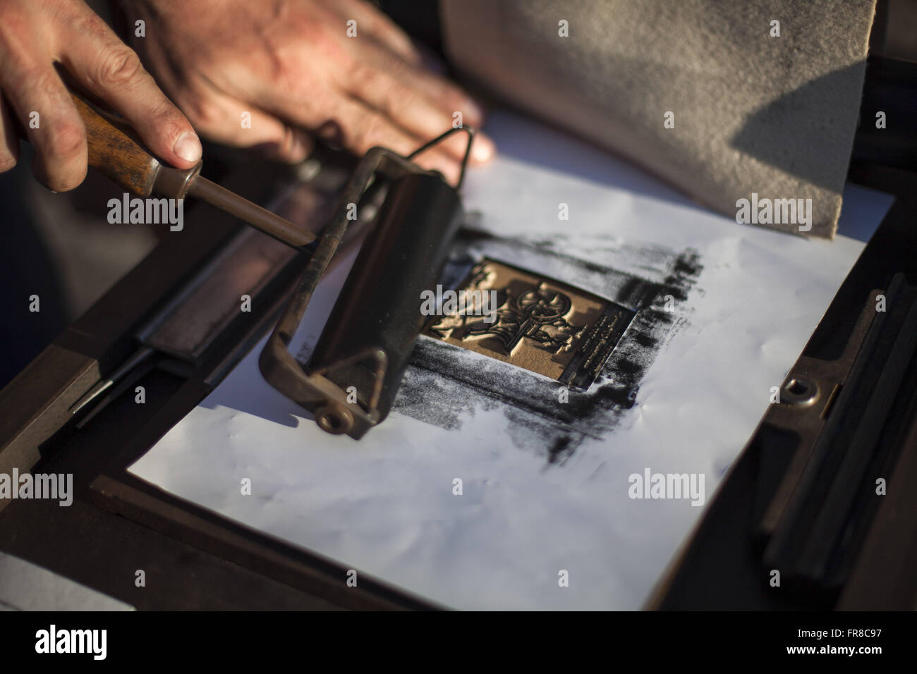 Working with woodcut on paper street artist - Stock Image