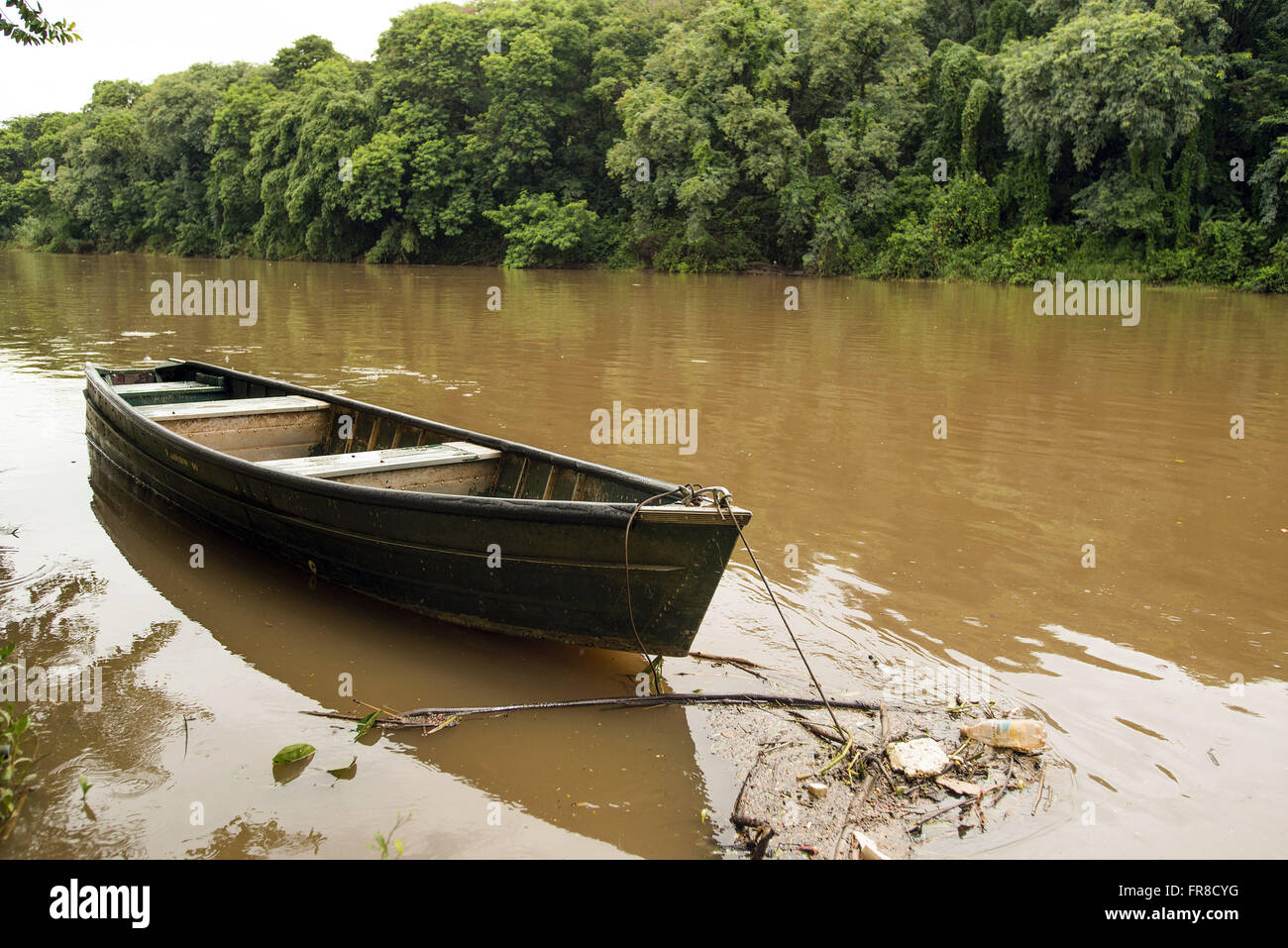Canoe anchored in Rio Piracicaba polluted - Stock Image