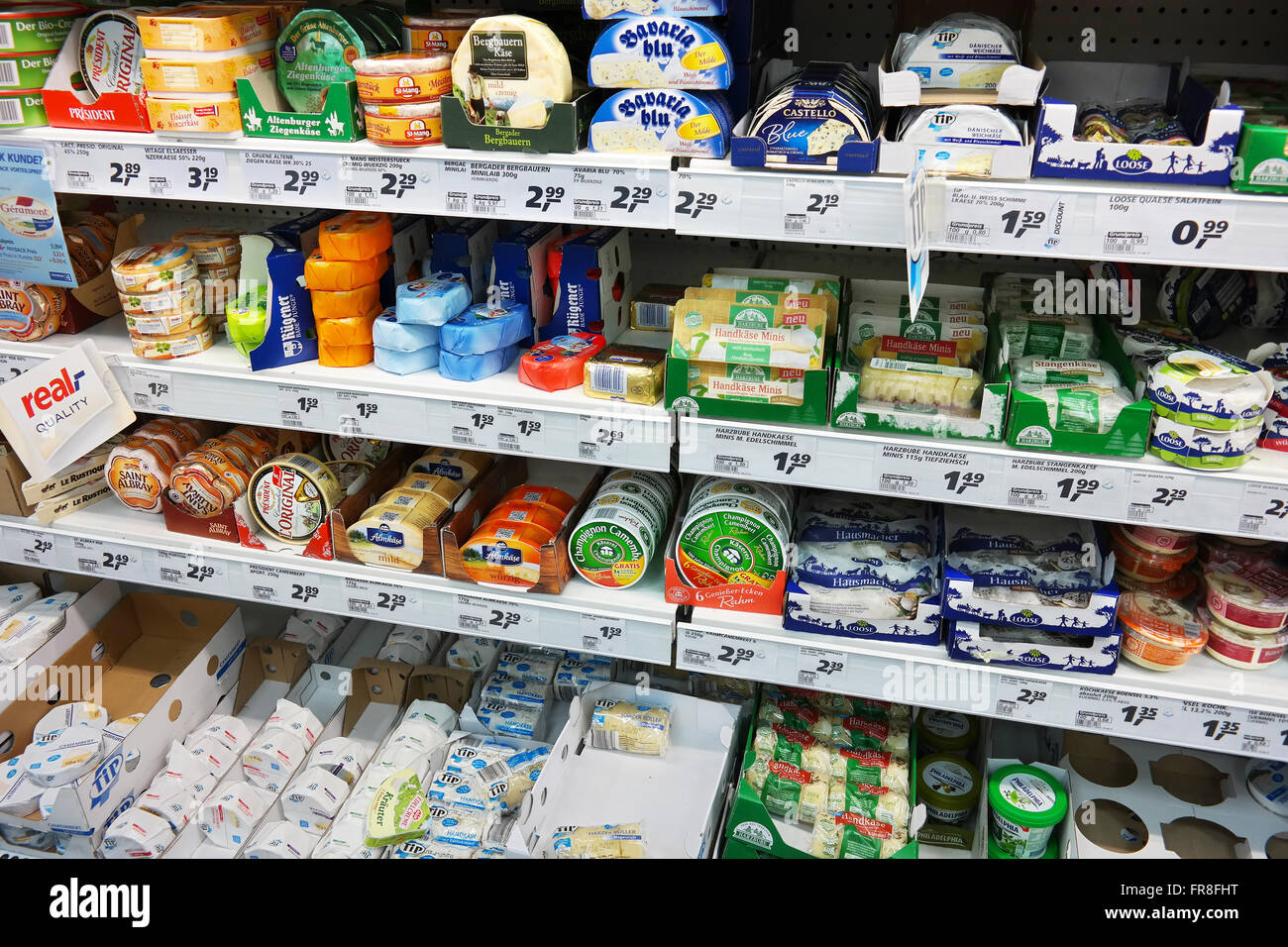 Assortment of wrapped European soft Cheeses in a store cooler of a Real Hypermarket. - Stock Image