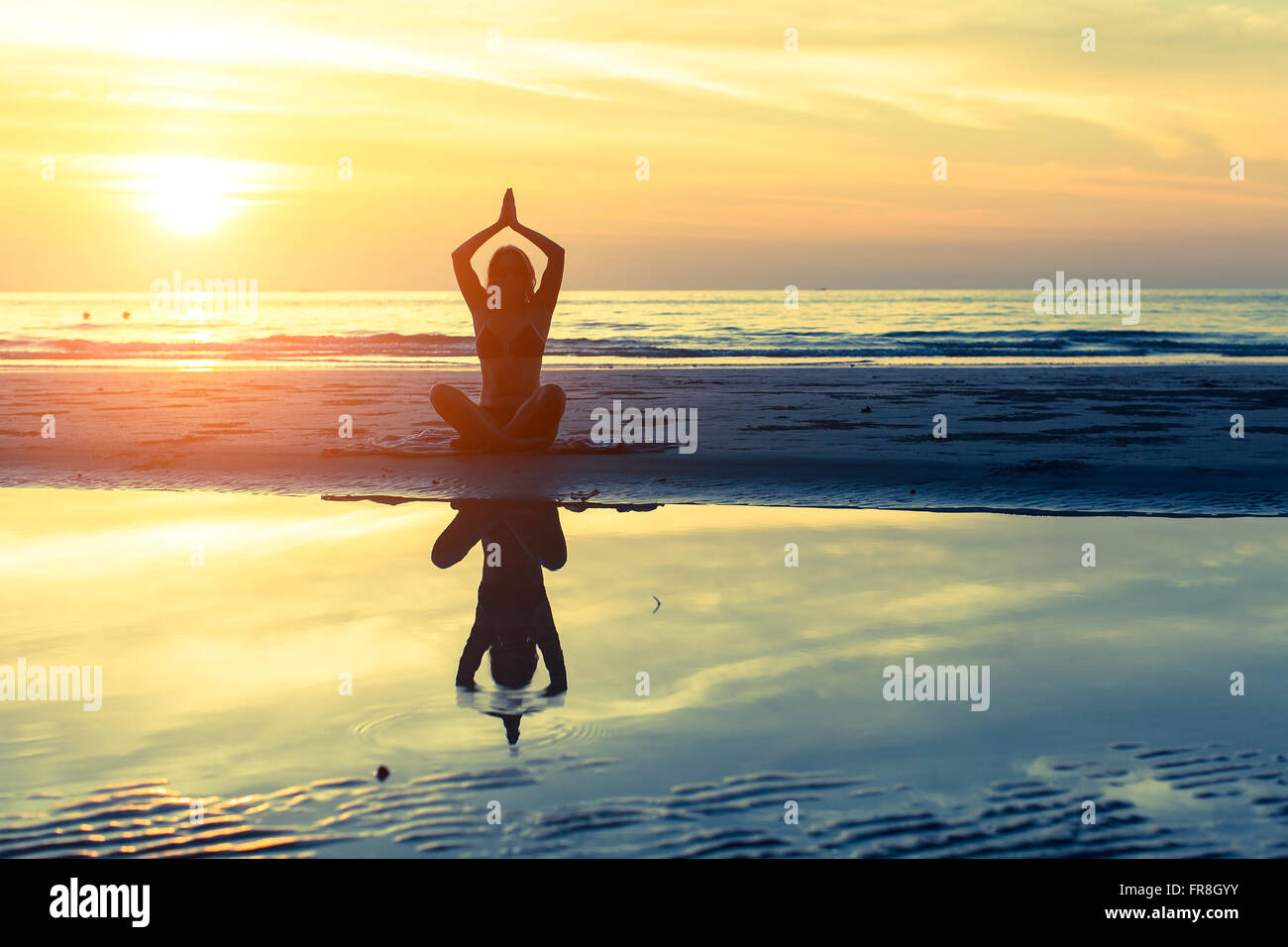 Silhouette yoga woman sitting on the beach with reflection in water at sunset. - Stock Image