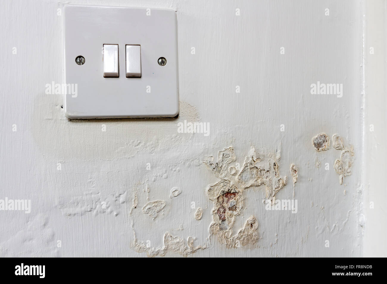 Damp Leaching Out of a Wall and Around a Light Switch in a Rented House Where the Landlord has Failed to Address - Stock Image