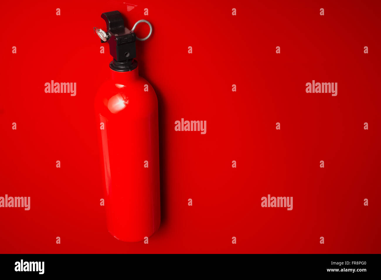 A small fire extinguisher hanging on a red wall ready to use. The lock pin and sealing is intact. - Stock Image