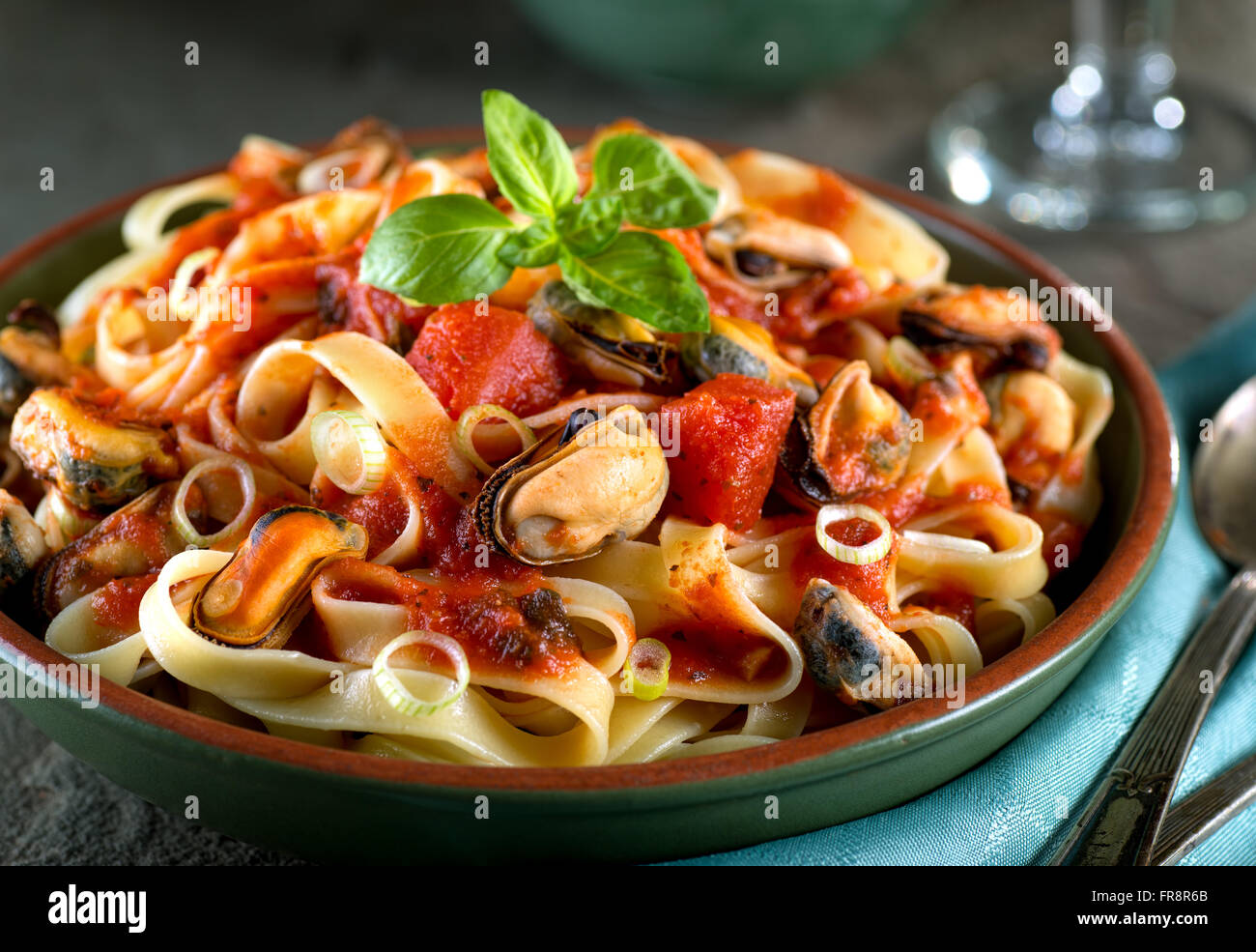 Delicious pasta with mussels in basil marinara sauce. Stock Photo