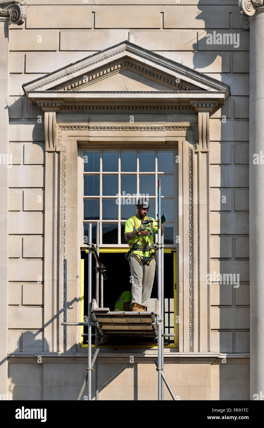 London, England, UK. Workman on scaffolding by a government building in Whitehall Stock Photo
