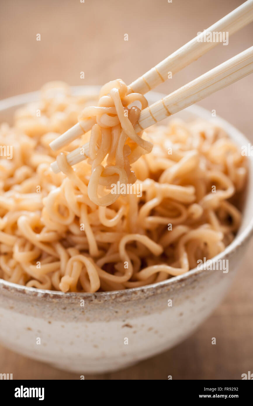 Ramen noodles in a traditional ceramic bowl with chopsticks shot with shallow focus - Stock Image