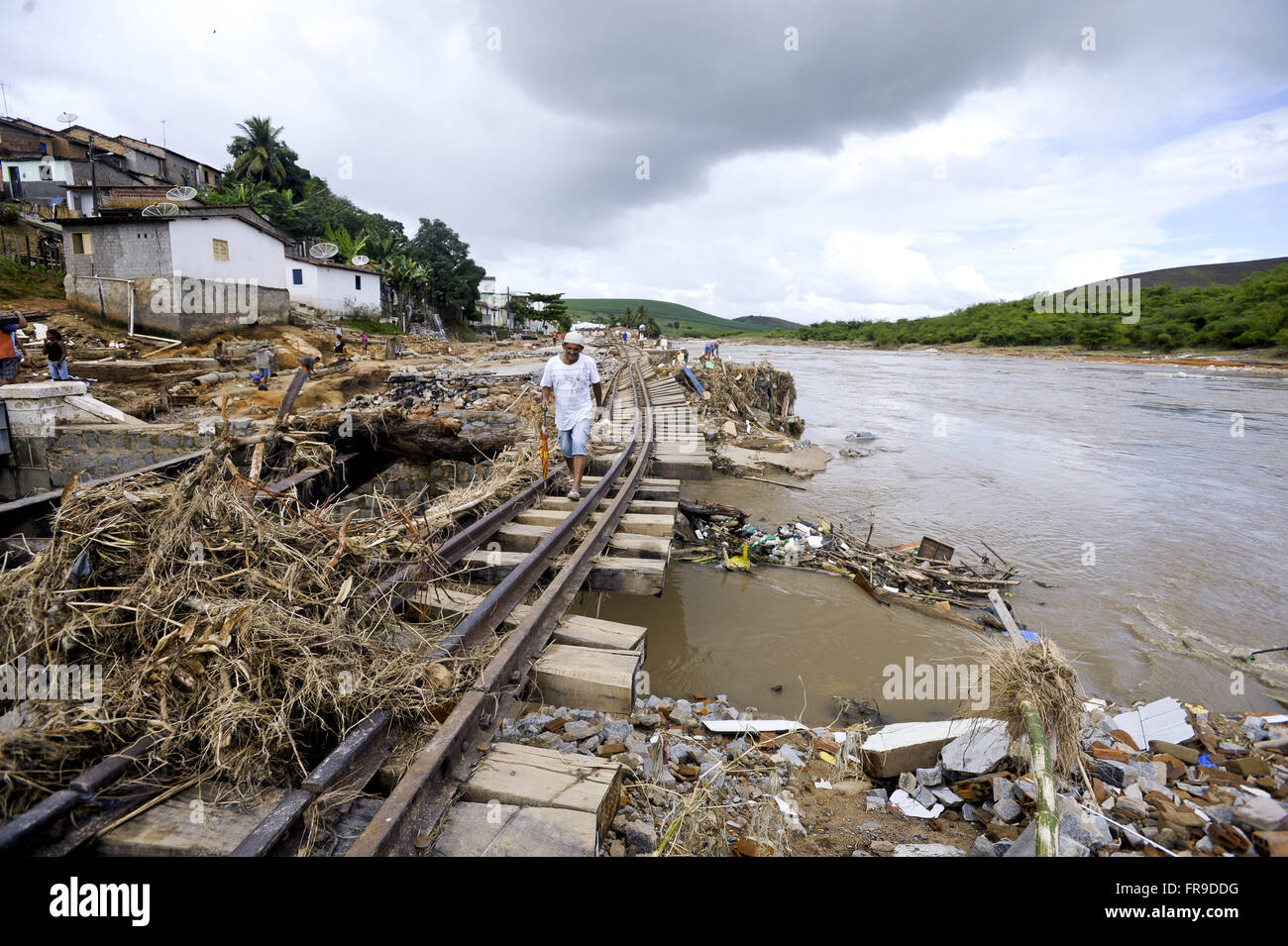 Man walking on the tracks of the Northeastern Railway Company with debris of houses and trade - Stock Image