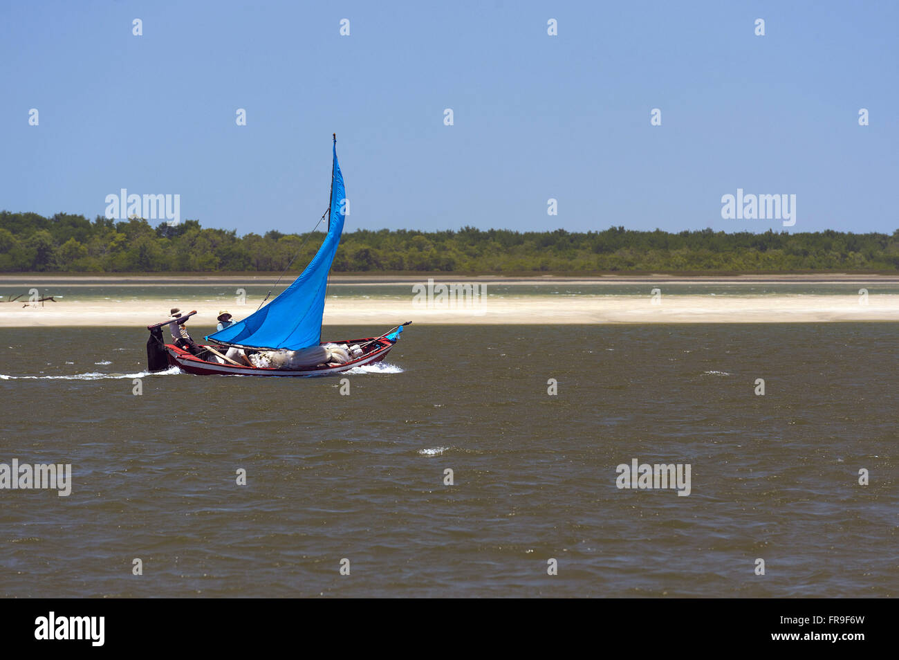 Wooden boat powered sailing in Rio Preguicas Stock Photo