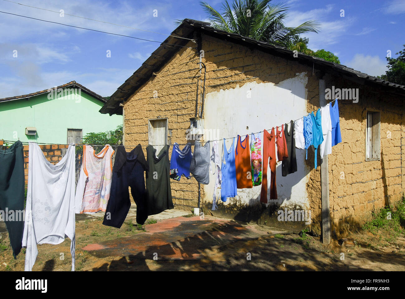 Clothesline with clothes in the backyard of house wattle-and-daub - Stock Image