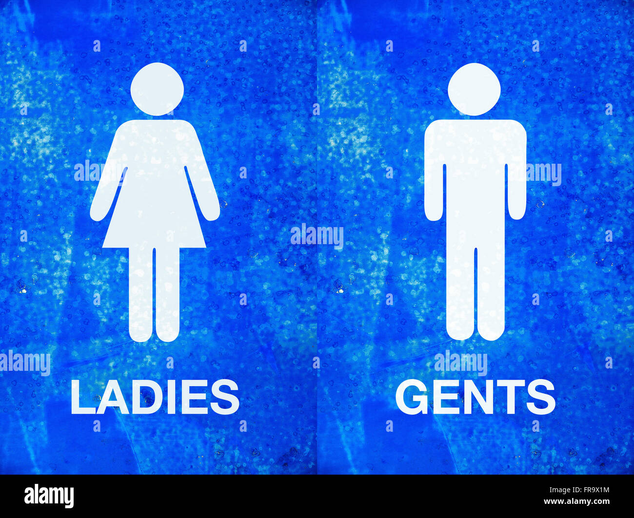 Ladies and gentlemen toilet sign on blue painted grunge texture - Stock Image