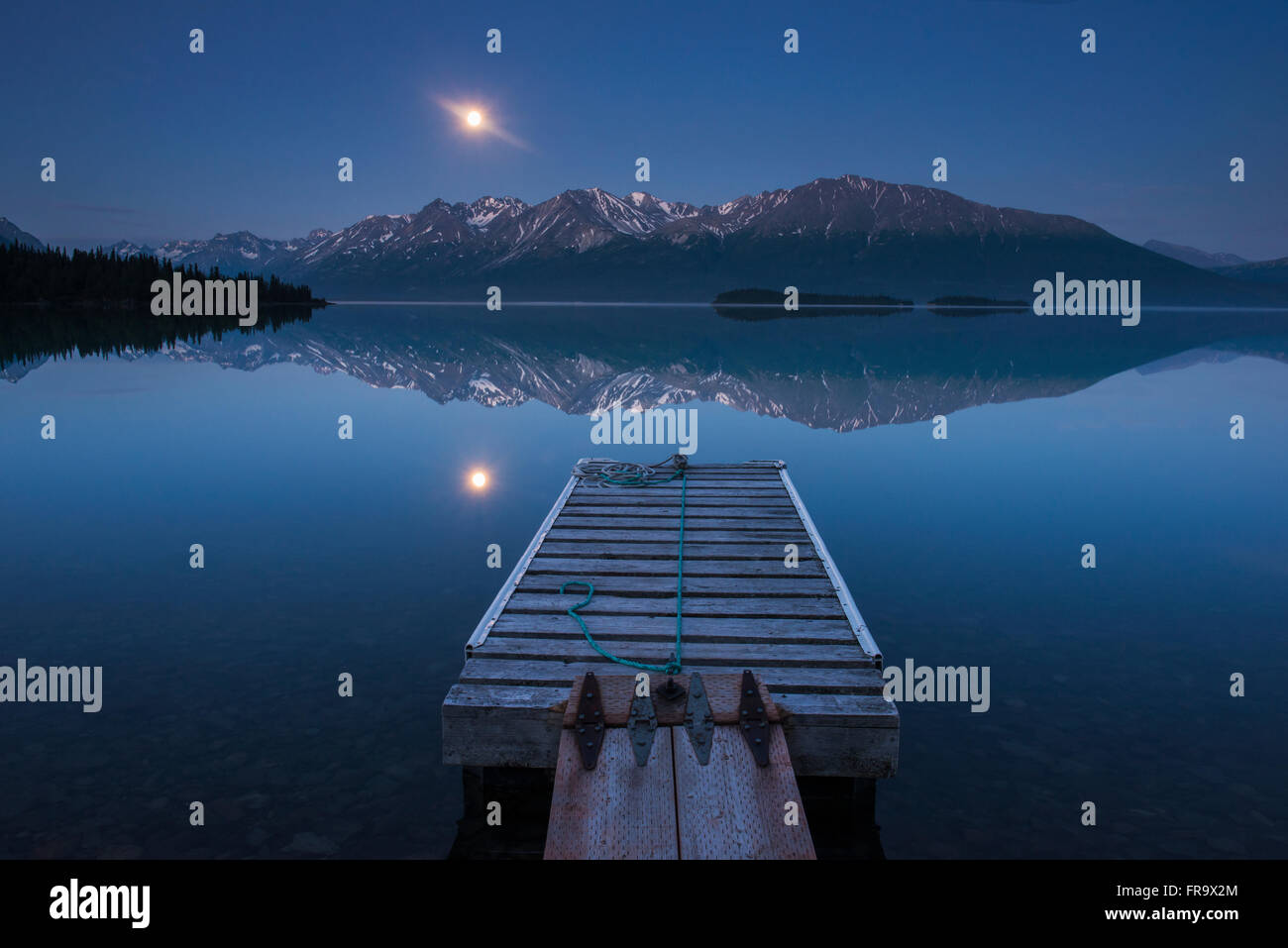 Boat dock with a full moon rising over the Chigmit Mountains at Lake Clark in Lake Clark National Park and Preserve, - Stock Image